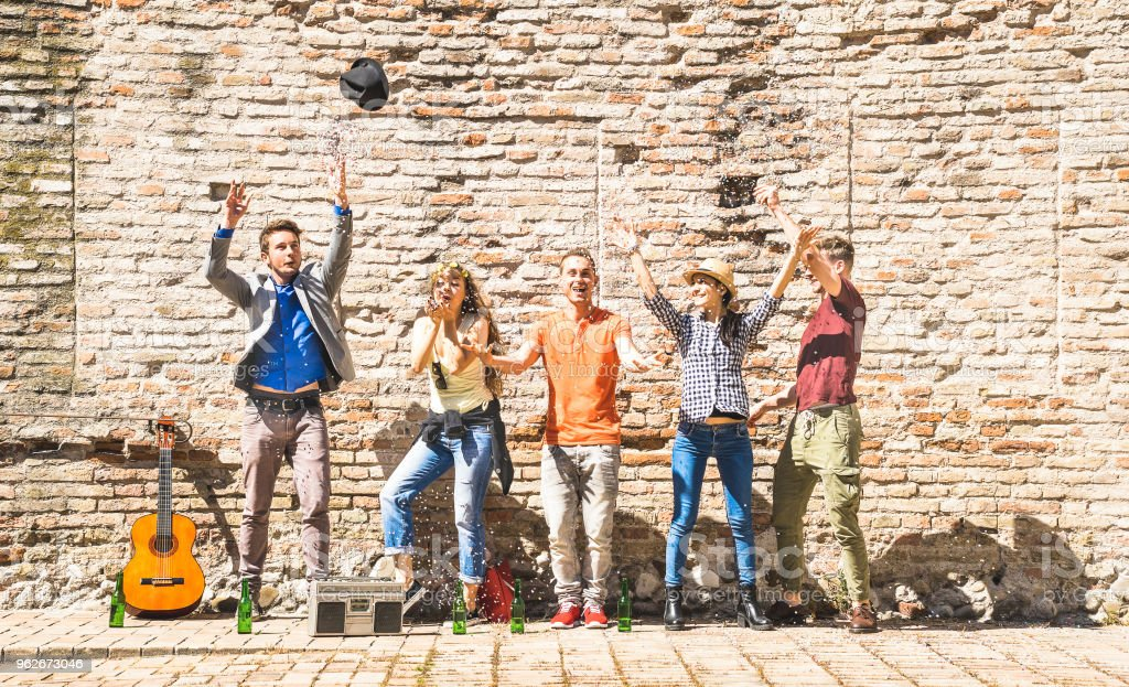 Happy friends group having fun outdoor cheering with confetti and beer bottles - Young people enjoying summer time together at urban party - Youth friendship concept on warm afternoon color filter stock photo