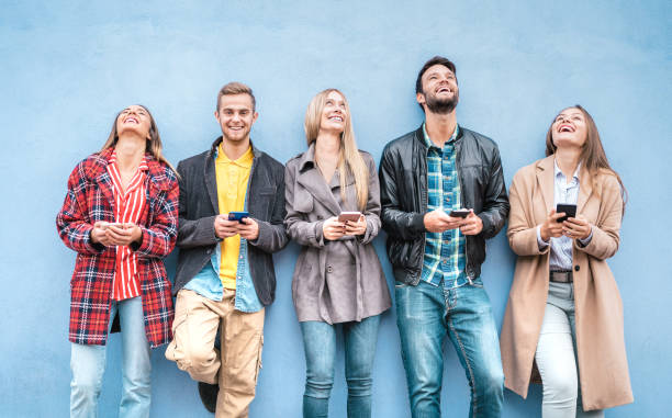 Happy friends group using smartphones against blue wall at university college break - Young people having fun with mobile smart phone - Technology addiction concept with always connected millennials stock photo