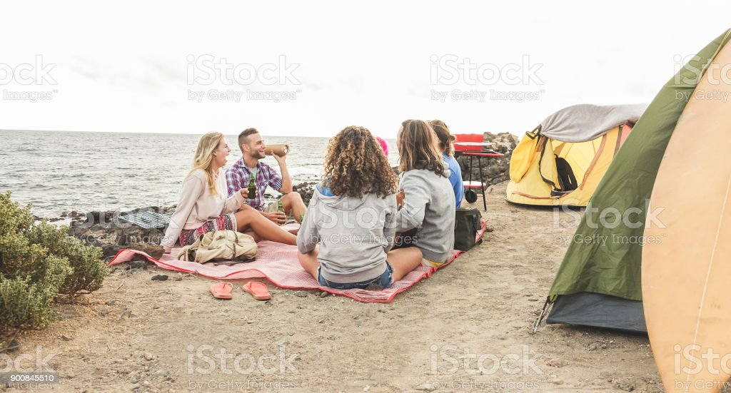 Happy friends having barbecue picnic next to the ocean - Trendy people having fun playing music, camping and laughing together in holidays - Travel, vacation, party and friendship concept stock photo