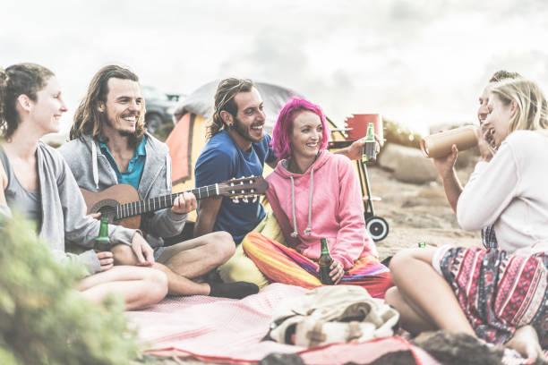 glückliche freunde picknick grill party am strand - erwachsene menschen camping, musizieren, lachen und trinken bier zusammen - freundschaft, spaß und natur-konzept - fokus auf mitte paar gesichter - tanz camp stock-fotos und bilder