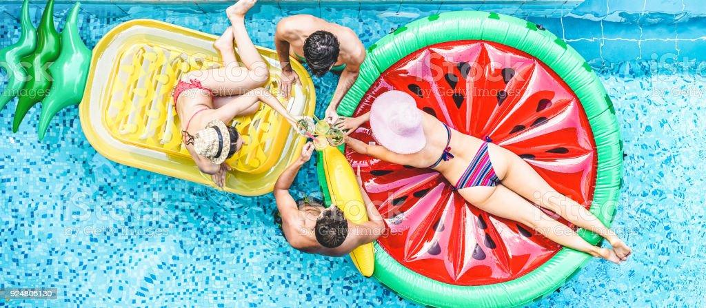 Glückliche Freunde jubeln mit Cocktails im Schwimmbad pa – Foto