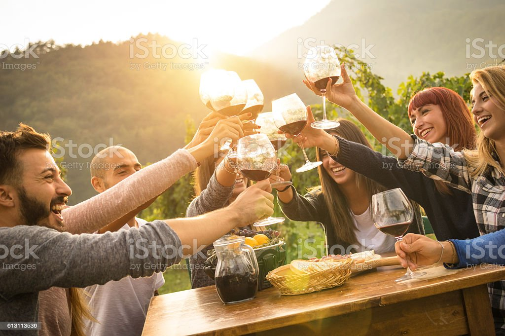 Happy friends having fun an drinking wine in autumn time - foto de stock