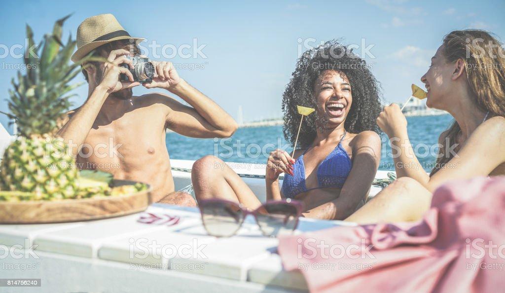 Amigos felizes, se divertindo e comendo fruta abacaxi fresco na festa do barco - jovens tirando fotos no mar do Caribe tour - juventude, tropical, viajam e conceito de férias de verão - foco na deixou caras - foto de acervo
