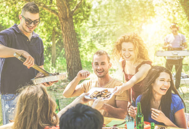 Happy friends having fun at barbecue party drinking beer, eating ,listening music - Young people enjoying bbq dinner outdoor - Friendship and summer concept - Warm filter - Focus on center blond guys stock photo
