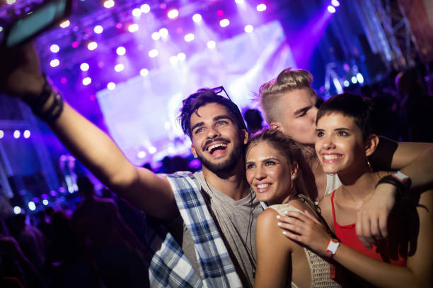 Happy friends having fun at music festival stock photo