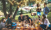 Happy friends having fun at vineyard after sunset - Young people millennial camping at open air picnic under bulb lights - Youth friendship concept with young people drinking wine at barbecue party