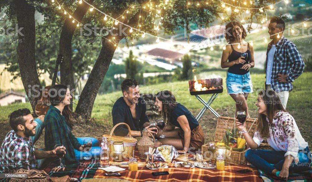 幸せな友達を持つ - 電球のライトの下で野外ピクニック キャンプの若者の千年 - 日没後の畑で楽しい若い青年友情概念人バーベキュー パーティーでワインを飲んだり ストックフォト