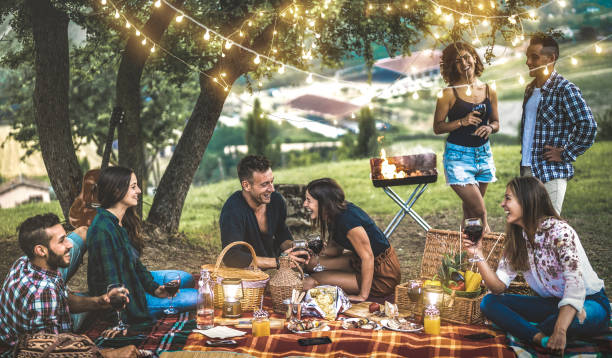 Happy friends having fun at vineyard after sunset - Young people millennial camping at open air picnic under bulb lights - Youth friendship concept with young people drinking wine at barbecue party stock photo