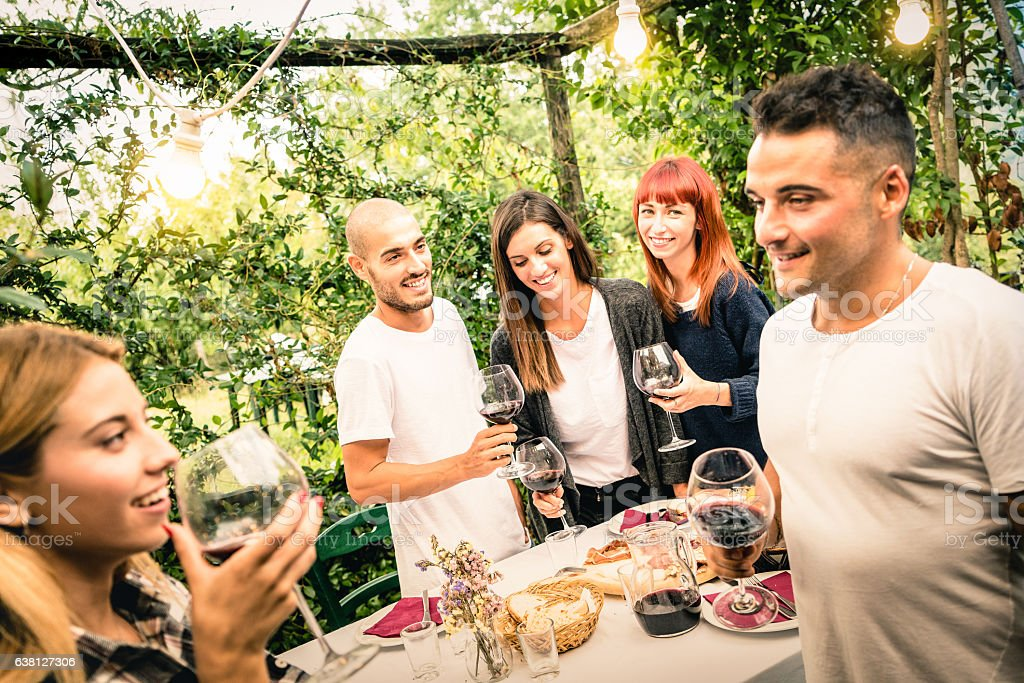 Happy friends having fun drinking red wine at garden party stock photo