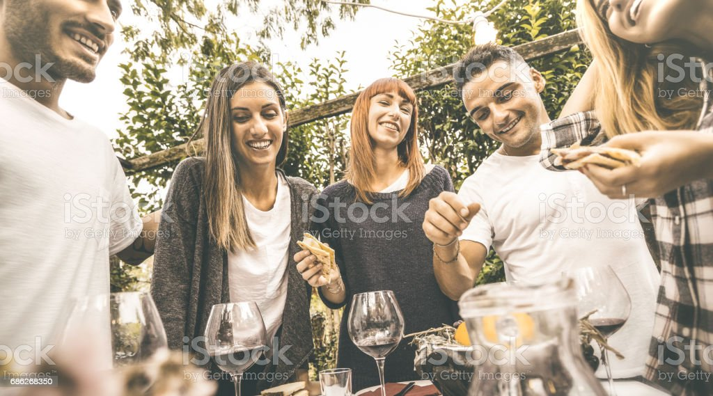 Happy friends having fun drinking red wine eating at garden party - Friendship concept together at farmhouse vineyard winery - Focus on girl in middle with retro desaturated opaque contrast filter stock photo