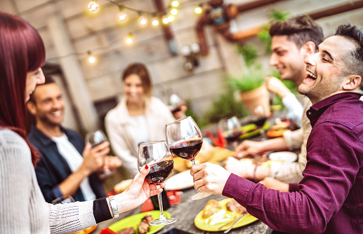 Happy friends having fun drinking red wine on balcony at private dinner party - Young people eating bbq food at fashion restaurant together - Dining lifestyle concept on warm filter - Focus on glasses