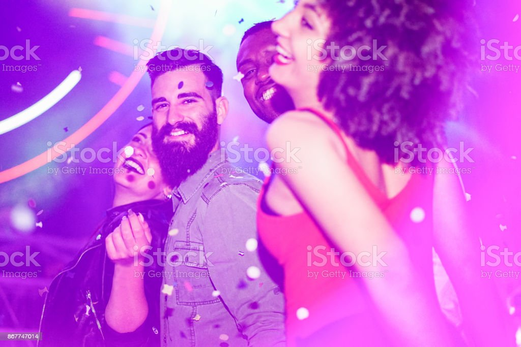 Happy friends having fun in night club with canon ball throwing confetti - Young people enjoying weekend nightlife with original laser lights color - Soft focus on bearded white man - Warm filter royalty-free stock photo