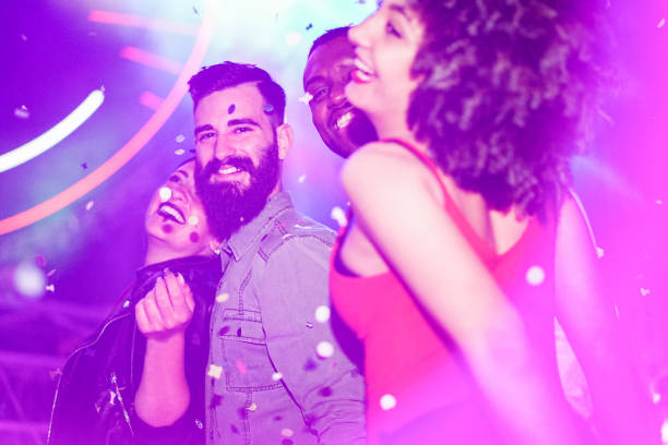 Happy friends having fun in night club with canon ball throwing confetti - Young people enjoying weekend nightlife with original laser lights color - Soft focus on bearded white man - Warm filter stock photo