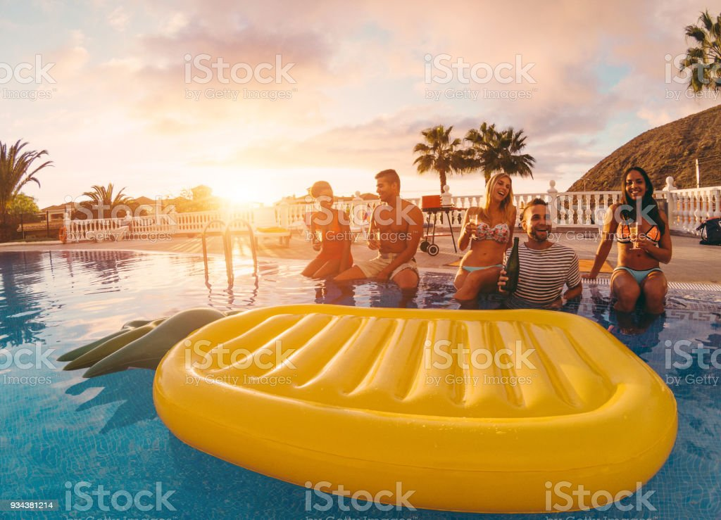Happy friends having fun in pool party at sunset - Rich people drinking and laughing in exclusive tropical vacation - Holiday and friendship concept - Main focus on right guys stock photo