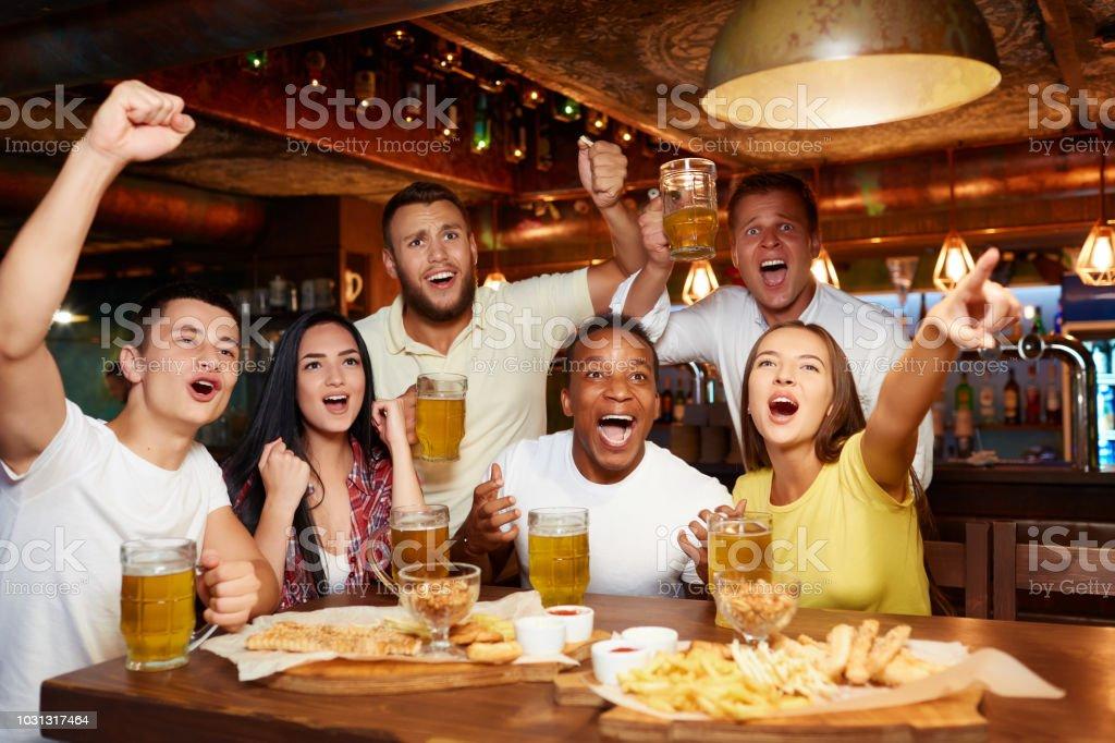 Amis heureux s'amuser dans la pub, je regarde le sport à la télévision ensemble. photo libre de droits