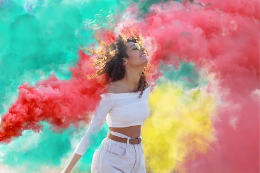 Beautiful young woman surrounded  light up colored smoke bombs - Happy friends having fun in the park with multicolored smoke bombs - Young students celebrating spring break together. Holi festival.