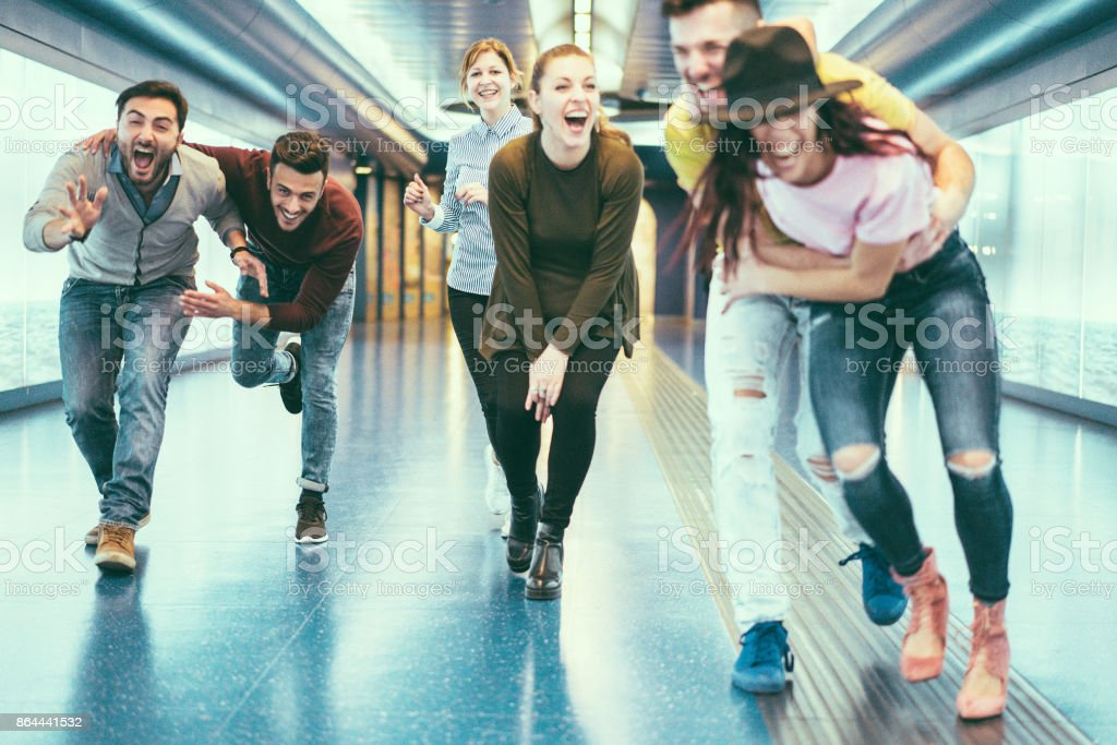 Happy friends having fun in underground metropolitan station - Young people hanging out ready for party night - Friendship, happiness and youth concept - Retro camera filter - Focus on left woman face stock photo