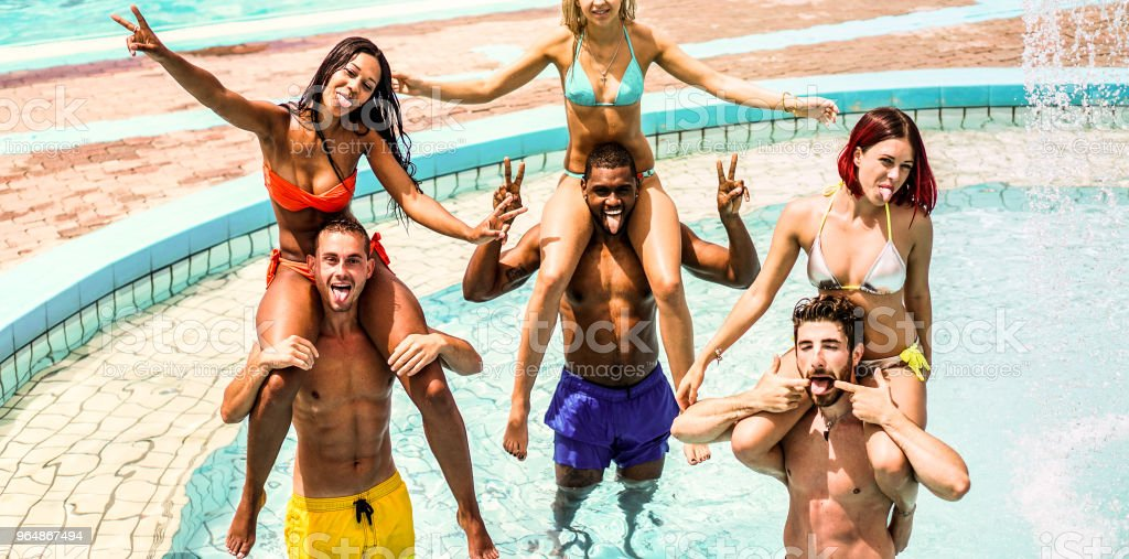 Happy friends having fun in water aqua park on summer vacation - Young diverse culture couples playing in swimming pool - Holidays concept - Main focus on left guys - Warm contrast filter royalty-free stock photo