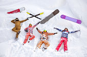 Four happy friends skiers and snowboarders are having fun and lying on snow with ski and snowboards. Aerial view