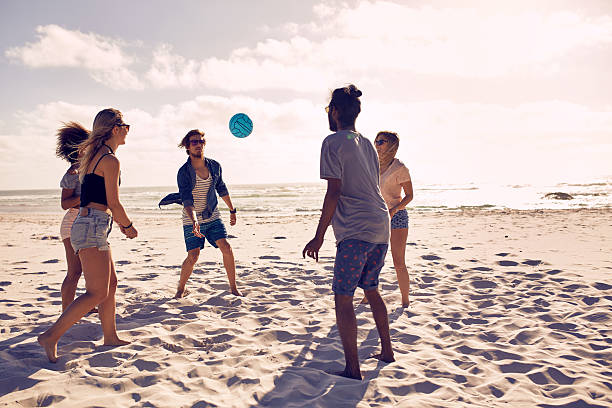 happy friends having fun on the beach - volleyball sport stock photos and pictures