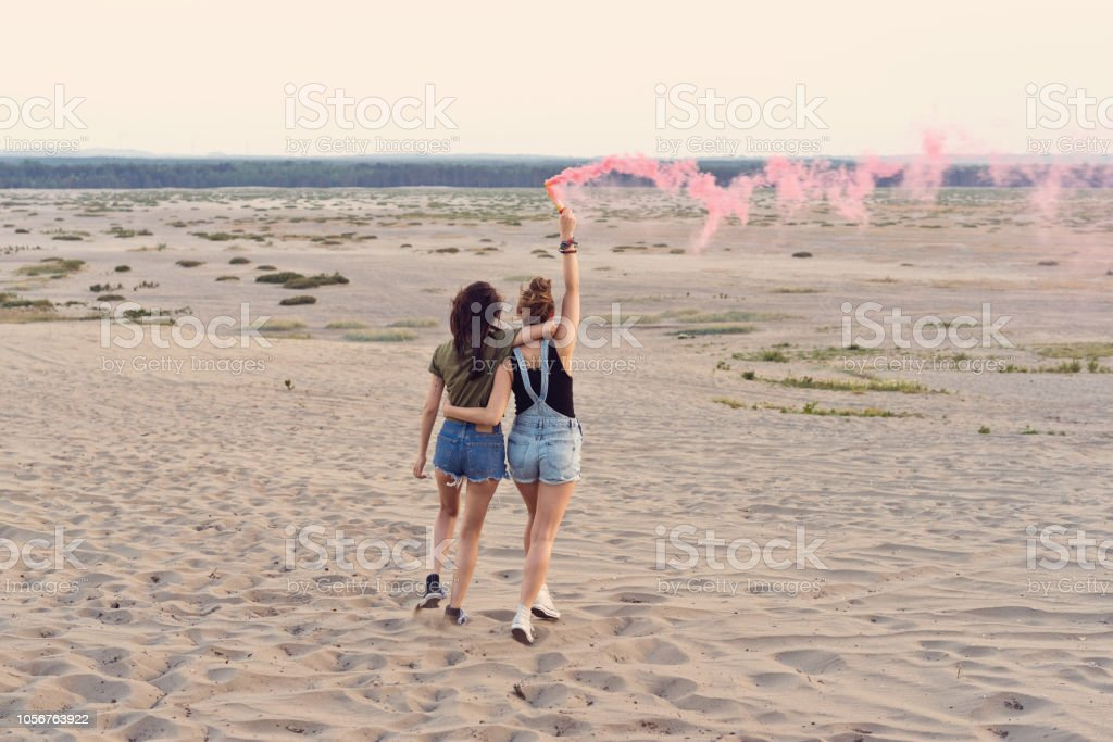 Happy friends having fun on the desert, holding distress flare Back view of two young women having fun on the dune, holding distress flare in hand. Adolescence Stock Photo