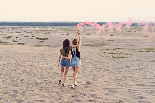 Happy Friends Having Fun On The Desert Holding Distress Flare Stock Photo - Download Image Now