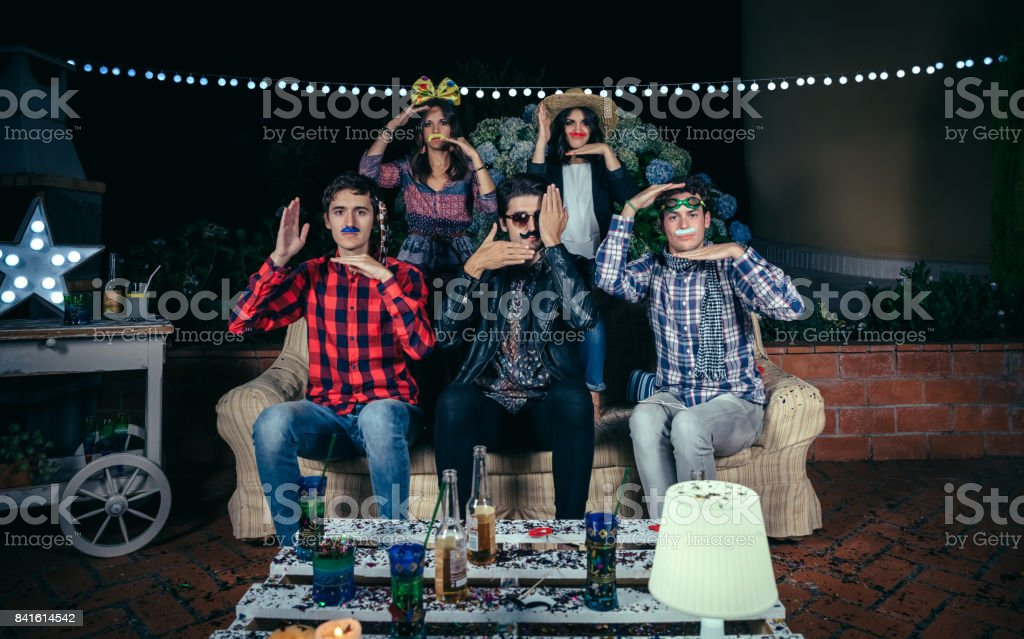 Happy friends having fun with costumes in party stock photo