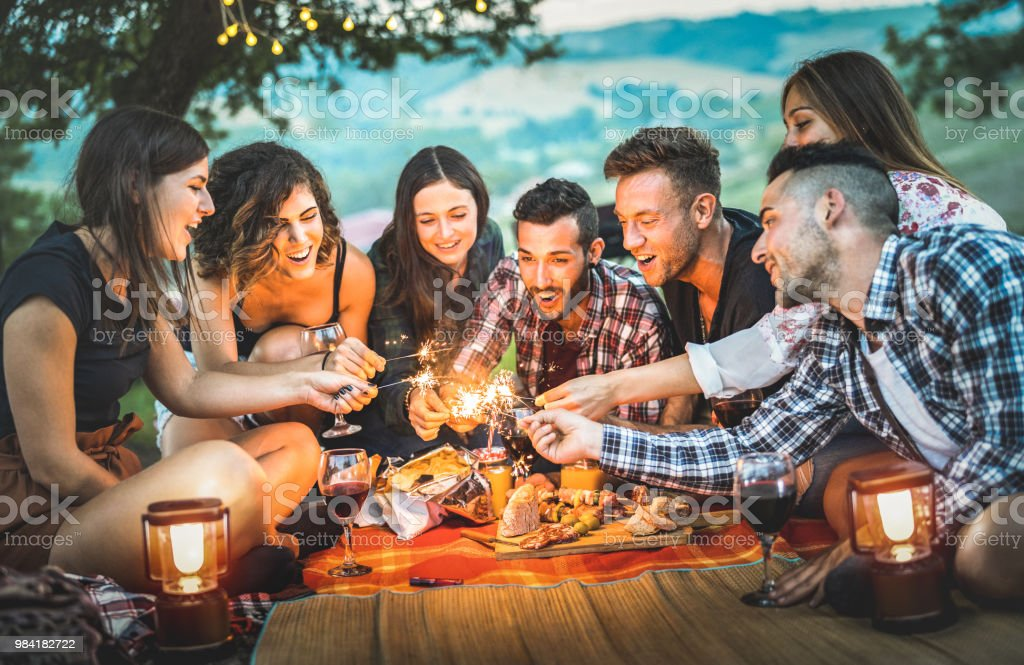 Happy friends having fun with fire sparkles - Young people millennials camping at picnic after sunset - Young people enjoying wine at summer barbecue party - Youth friendship concept on night mood стоковое фото