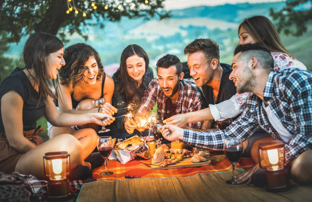 Cтоковое фото Happy friends having fun with fire sparkles - Young people millennials camping at picnic after sunset - Young people enjoying wine at summer barbecue party - Youth friendship concept on night mood