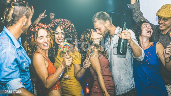 istock Happy friends having multiracial fun at new year's eve celebration - Young people drinking and dancing at after party in night club - Friendship concept on drunk mood - Focus on yellow cloth woman 1073517066