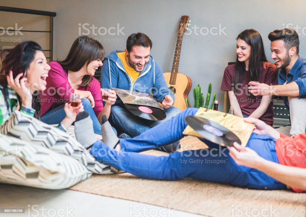 Happy friends having party listening vintage vinyl disc albums in hostel room - Young people having fun drinking shots and laughing together - Soft focus on left man face - Warm filter stock photo