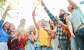 istock Happy friends having party,throwing confetti and using smoke bombs colors outdoor - Young students laughing and celebrating together - Youth concept - Main focus on three right guys faces 910450024