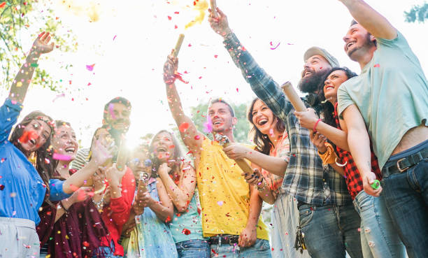 Happy friends having party,throwing confetti and using smoke bombs colors outdoor - Young students laughing and celebrating together - Youth concept - Main focus on three right guys faces stock photo