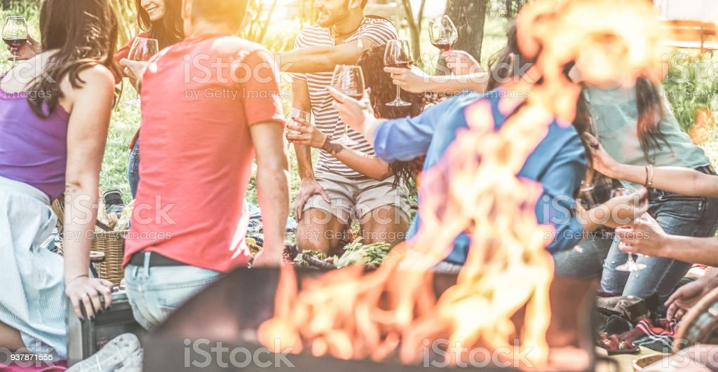 Happy friends having picnic dinner with barbecue in nature outdoor - Young people eating bbq meal and toasting wine - Focus on behind left guys - Youth lifestyle, summer and friendship stock photo
