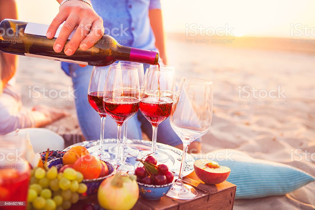 Happy friends having wine on the beach. Sunset beach party stock photo