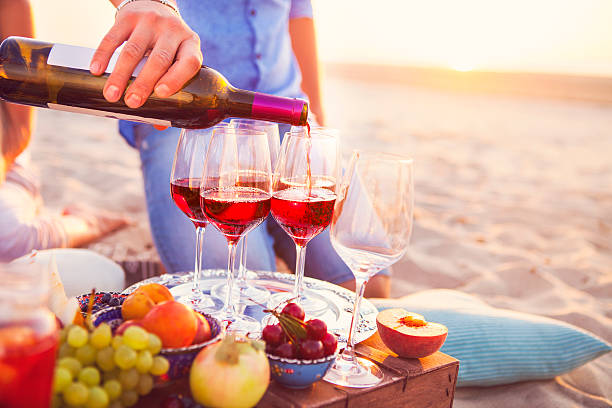 Happy friends having wine on the beach. Sunset beach party stock photo
