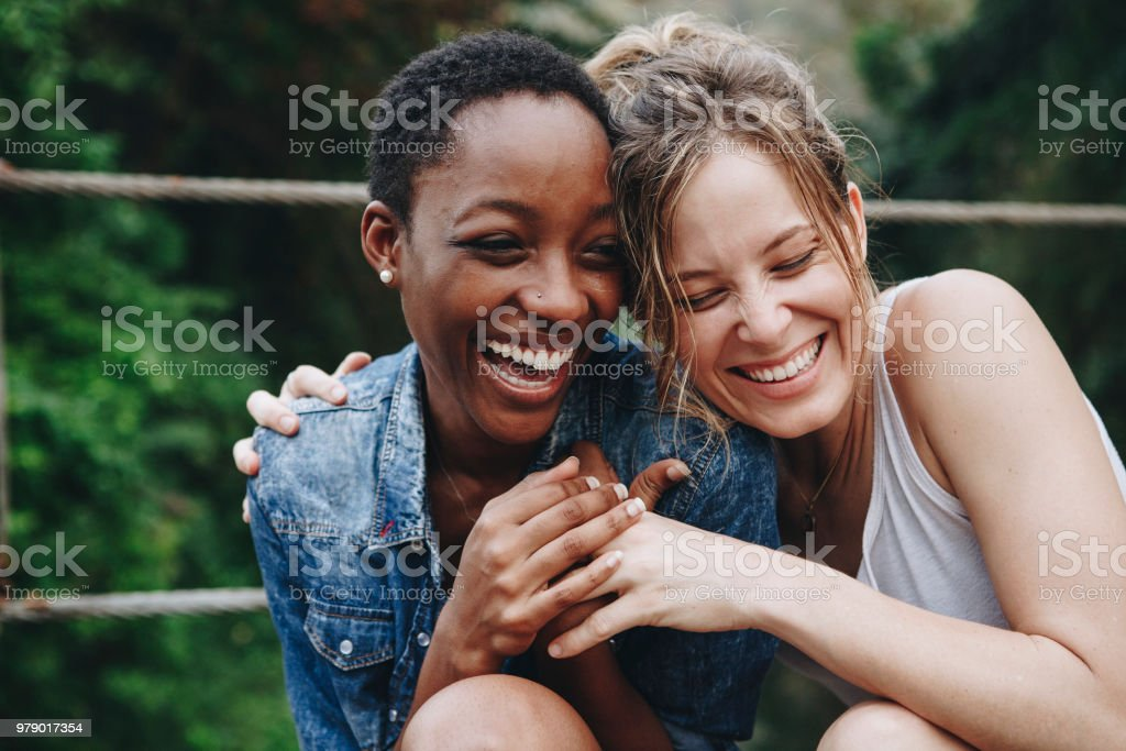 Happy friends holding each other stock photo