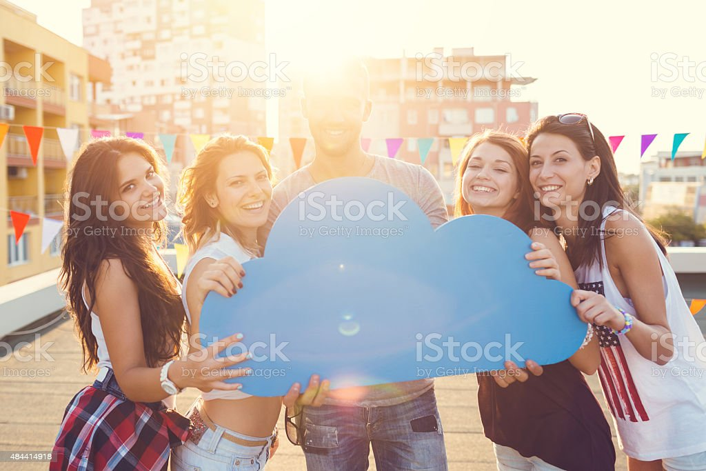 Happy friends holding speech bubble on the rooftop stock photo