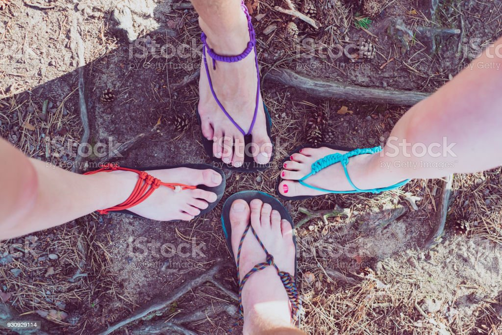 Happy friends in handmade barefoot sandals. Sandals made of rubber and strings. Minimalistic. Detail of feet. - foto stock