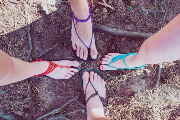 glückliche freunde in handarbeit barfuss sandalen. sandalen von gummi- und saiten. minimalistisch. detail der füße. - flip flops reparieren stock-fotos und bilder