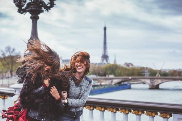 glückliche freunde in paris mit zerzausten haaren an windigen tag - genießen französisch stock-fotos und bilder
