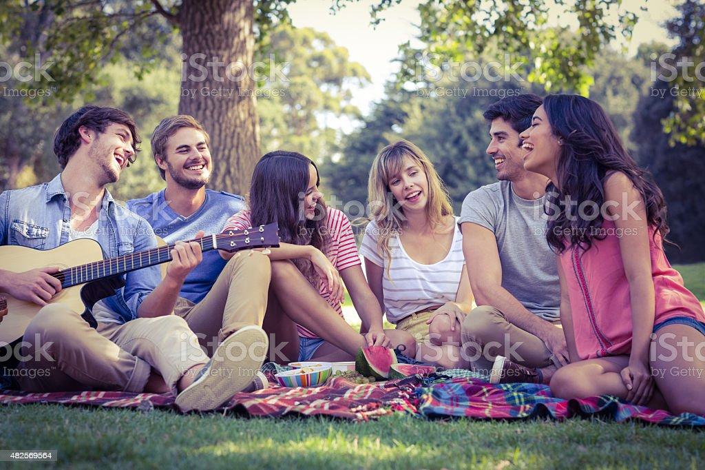 happy friends in park having a picnic stock photo