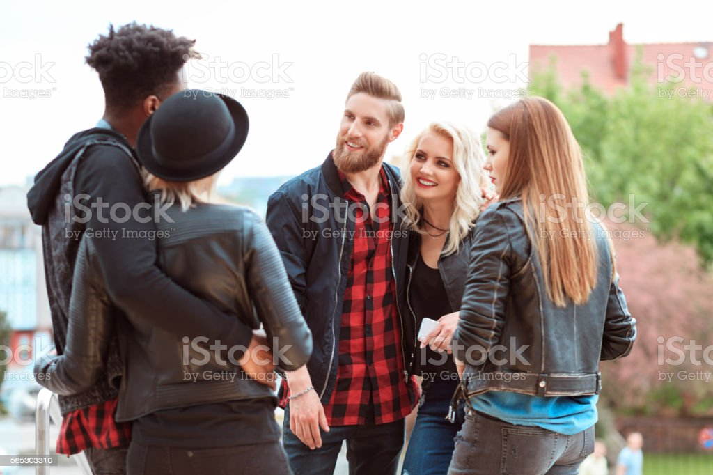 Happy friends in the city Multi ethnic group of young people talking outdoor in the city. 20-29 Years Stock Photo