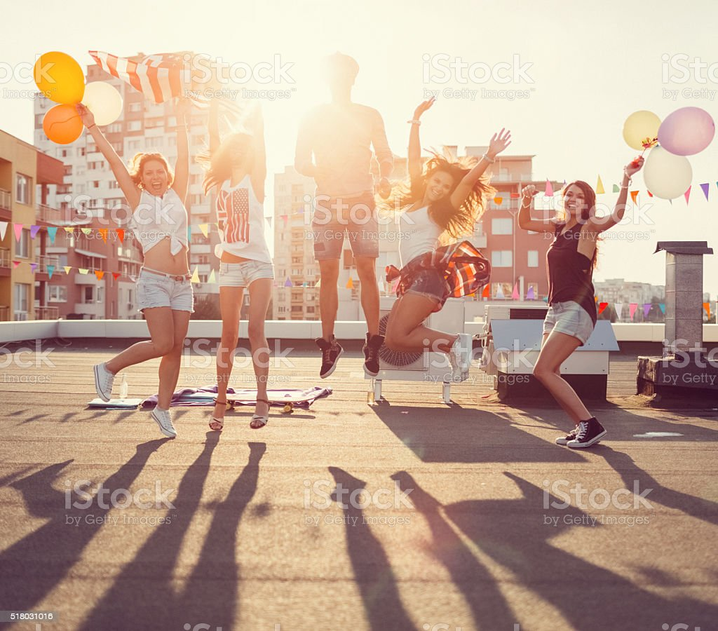 Happy friends jumping from joy on the rooftop stock photo