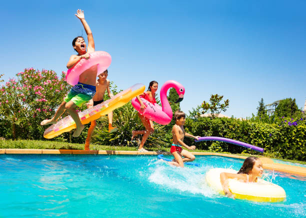 Happy friends jumping in pool on the vacations Group of age-diverse boys and girls, happy friends with swim floats jumping into swimming pool on the vacations mid air stock pictures, royalty-free photos & images