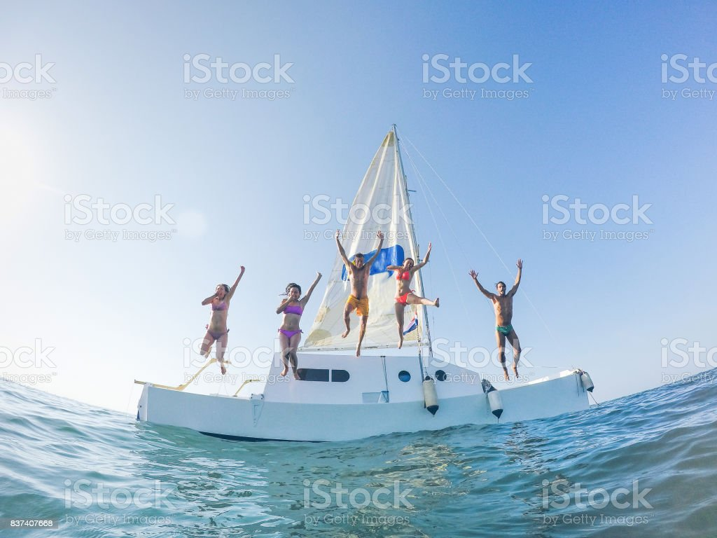 Happy friends jumping off the catamaran boat into the ocean - Young people having fun diving into the sea - Travel, tropical, summer and concept - Soft focus on center guys - Fisheye lens distorsion stock photo