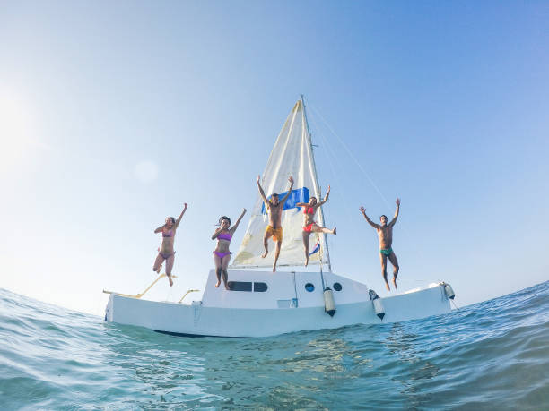 Happy friends jumping off the catamaran boat into the ocean - Young people having fun diving into the sea - Travel, tropical, summer and concept - Soft focus on center guys - Fisheye lens distorsion - fotografia de stock