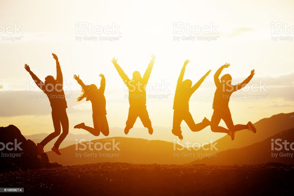 Happy friends jumping sunset mountains stock photo