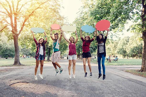 glückliche freunde springen und rede blasen in den händen - sprüche kinderlachen stock-fotos und bilder