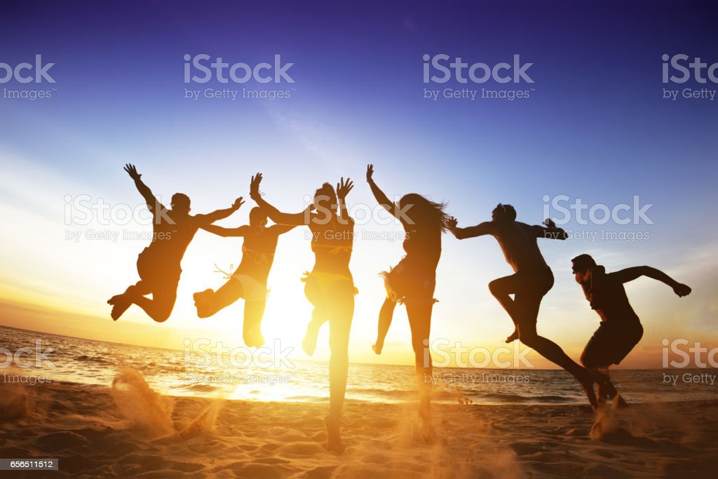 Happy friends jumps beach sunset. Friendship or team concept stock photo